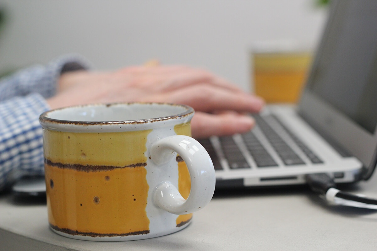 coffee mug closeup with man typing in background