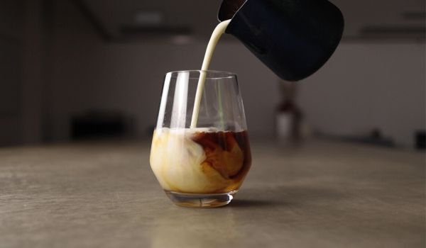 milk pouring into a glass of cold-brew